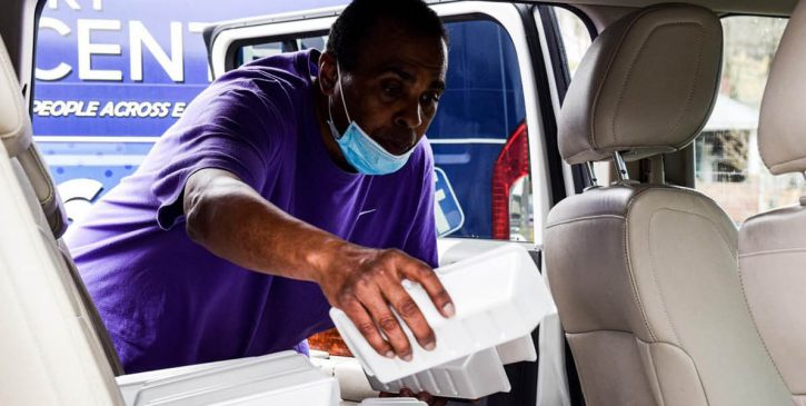 man putting boxed food into vehicle