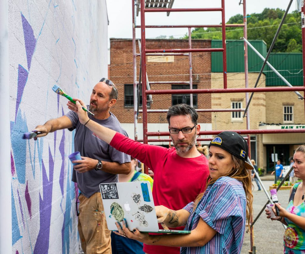 group of artist working together to design and paint mural