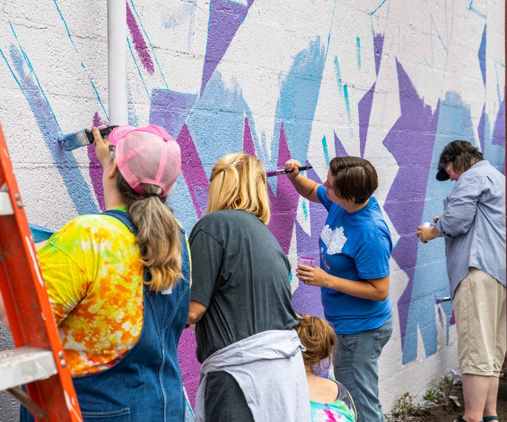 group of artist painting a mural