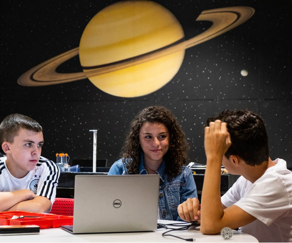 group of students sitting in front of a laptop